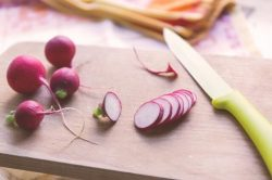 Chopping radishes on a chopping board with a sharp knife